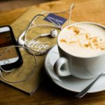 A cup of cofee and a smartphone with headphones plugged in
