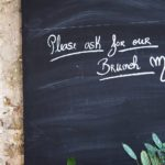 "A blackboard in a cafe with the words ""please ask to see our brunch menu!"" written on it."